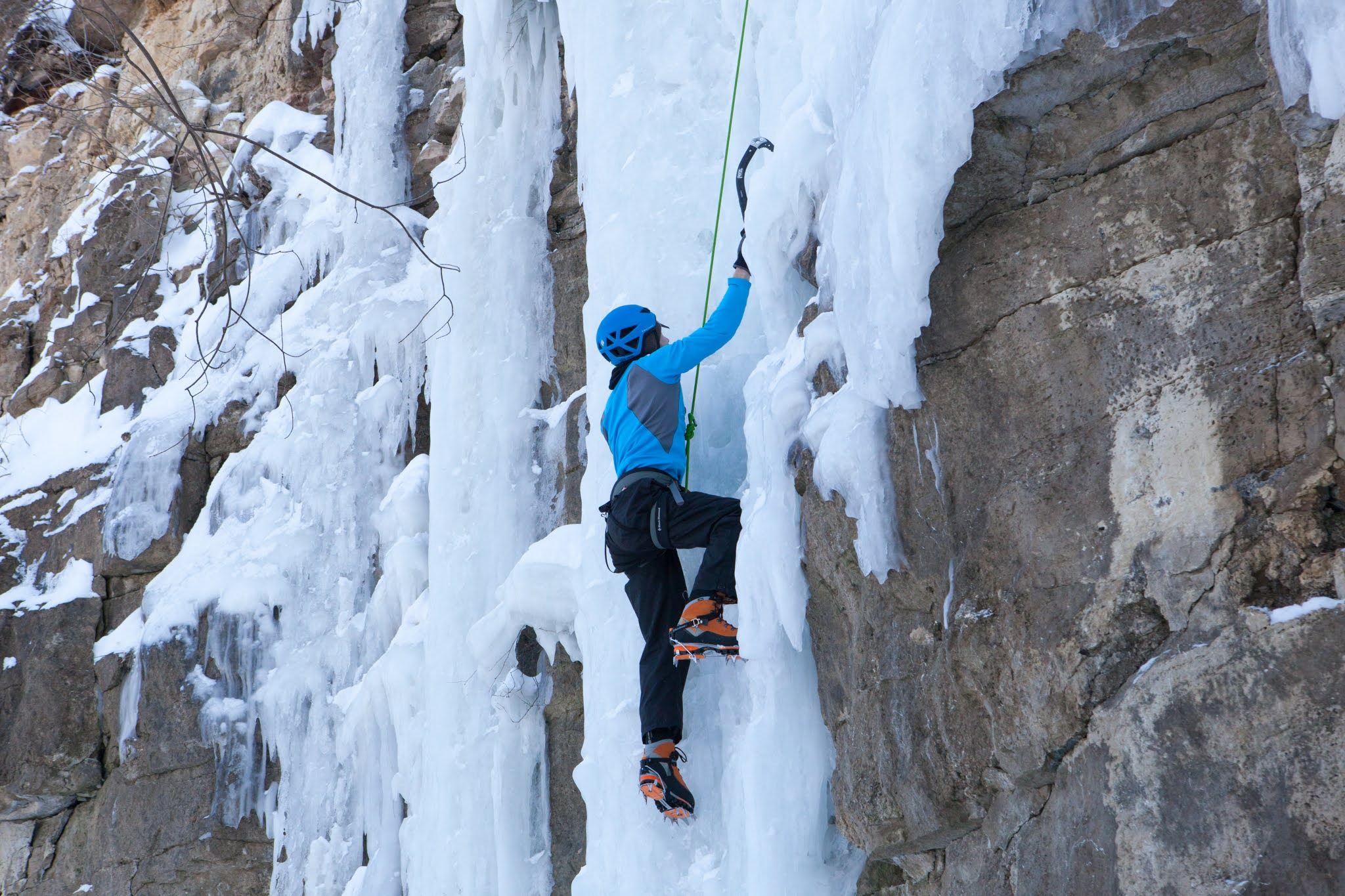 ice climber scales a rock and ice wall